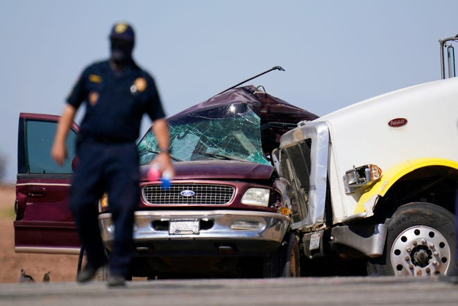 Law enforcement officers work at the scene of a deadly crash in Holtville, Calif., on March 2, 2021. Authorities say a semi-truck crashed into an SUV carrying multiple people on a Southern California highway, killing at least 13 people and injuring others.