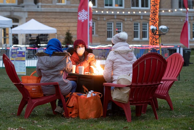 Students enjoy hot chocolate by a fire pit at Bowling Green State University as experts cite an increased confidence in heading out and about contributing to a robust economic recovery for the northwest Ohio region.