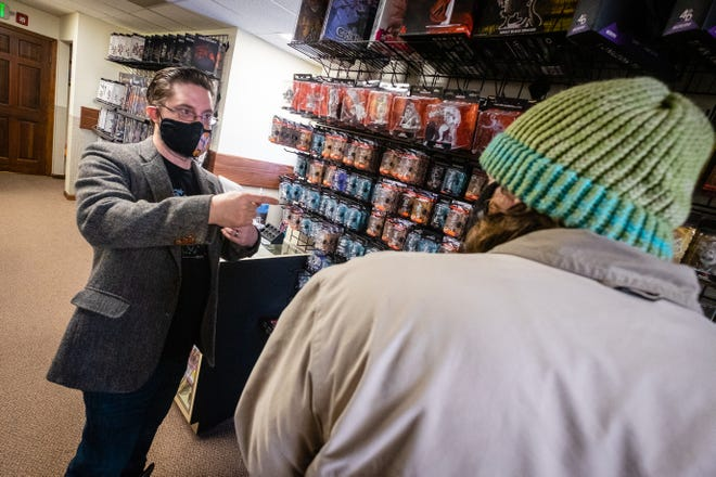 Derek Helsom, co-owner of Border Keep Games, talks with a customer Wednesday, March 3, 2021, in the store.
