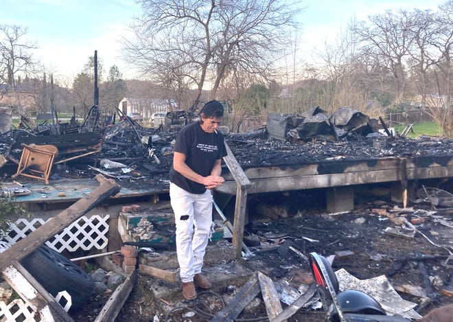 Bob Portz looks through the remains of a friend's house that burned down on Ridge View Road in Mountain Gate on Monday night.