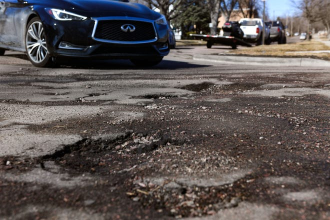 A car approaches an intersection littered with potholes on Wednesday, March 3, 2021, in Sioux Falls.