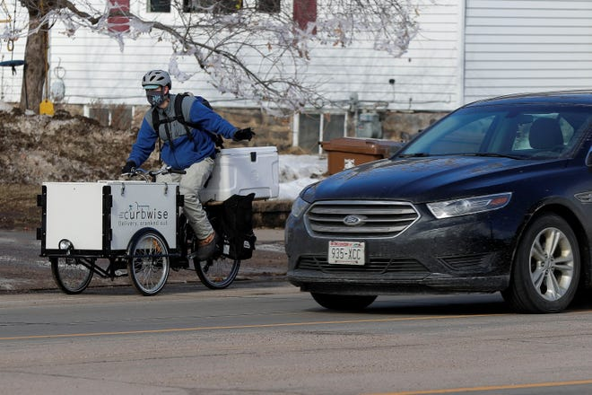 Trevor Roark signals a turn while on a delivery route in February in Stevens Point. Roark started Curbwise, a delivery service using a specialized tricycle, after he lost his job as a program manager for UWSP Adventure, a travel program at the university, due to the coronavirus pandemic.