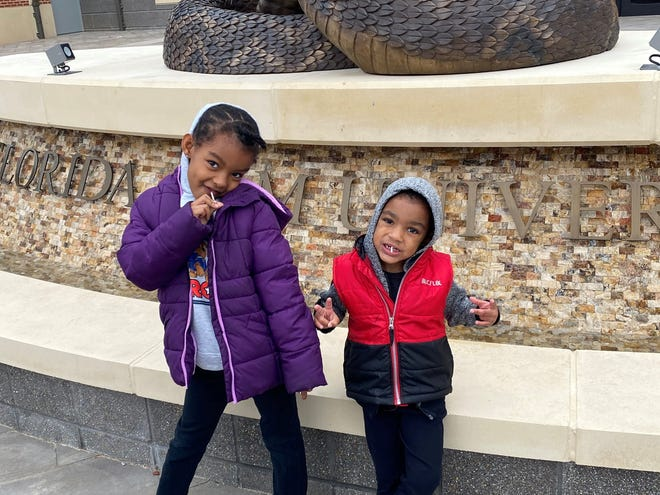 Ayana Standifer, 6, and Derrick Standifer Jr., 4, pose in front of the Rattler sculpture at FAMU, where their father is a Ph.D. student.