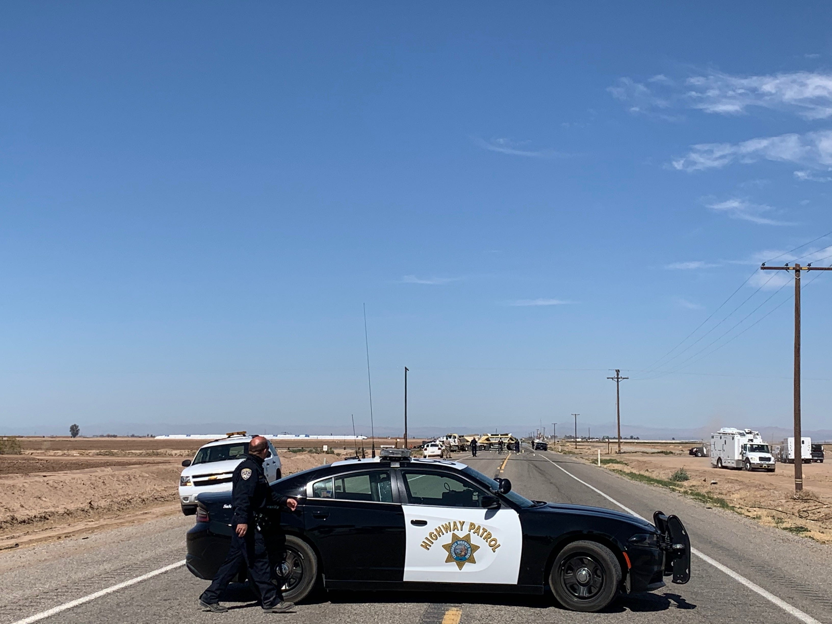 Police push reporters back from the scene on the side of State Route 115 near Holtville, Calif., as investigators scan the area from the sky Tuesday.