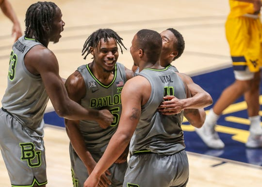 Baylor Bears guard Mark Vital (11) celebrates with teammates after defeating the West Virginia Mountaineers in overtime at WVU Coliseum.