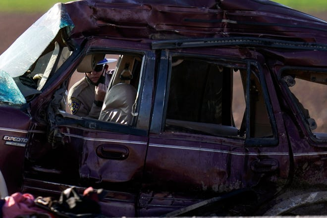 A California Highway Patrol officer examines the scene of a deadly crash in Holtville, Calif., Tuesday, March 2, 2021. Authorities say a semitruck crashed into an SUV, killing multiple people.