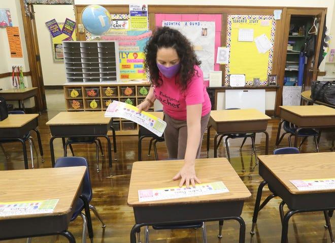 Pfeiffer Elementary School kindergarten teacher Janeen Beresh places name plates on desks Thursday as she prepares for the return of students.