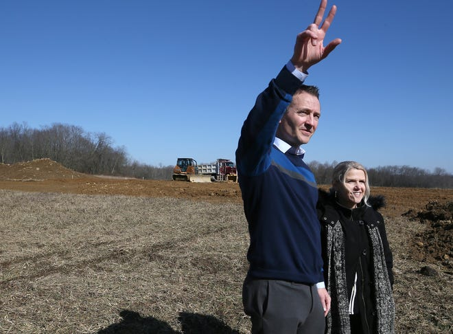 Dean Beddow waves at a passing neighbor Wednesday as he and his wife, Kris, talk about their wedding barn, Birdseye Barn at Western Star, the couple is building.
