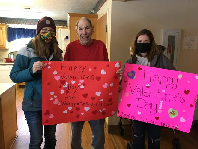 4-H adviser Lisa Parker and 4-H member Becca Buck hold Valentine's Day posters with Alliance Group Home resident Bruce Robertson.