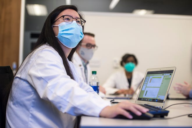 Second-year Medical College of Georgia student Jere Tan looks at a large wall-mounted computer screen as she and other students work on diagnostic scenarios during a class Thursday.