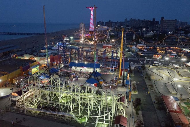 Coney Island rides and amusement park are illuminated after sundown in the Brooklyn borough of New York. Gov. Andrew Cuomo said that arcades and other indoor family entertainment centers can open with 25% capacity starting March 26. Outdoor amusement parks can open with a third of their normal capacity by April 9, while day and overnight camps can start planning for reopening this summer.
