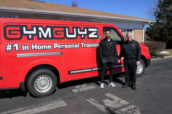GymGuyz franchise owner/operator Bill Alesio (right) and district manager Emmanuel Lewis show the mobile van they will use to take fitness programs to residents' homes and businesses Tuesday as the franchise joined the Lower Bucks Chamber of Commerce in Falls.