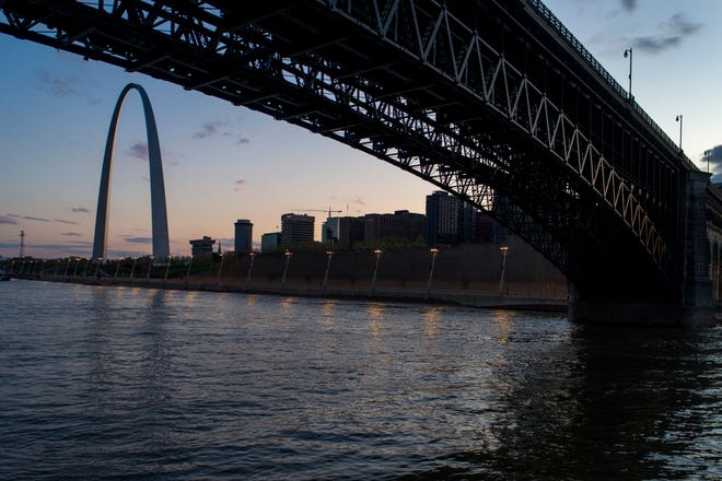 The Eads Bridge crosses the Mississippi River from Illinois to Missouri as the sun sets beyond the Gateway Arch last year in St. Louis.