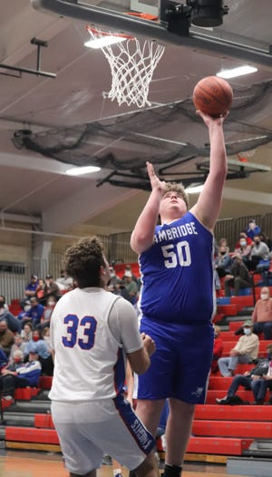 Cambridge senior Brock Valentine (50) goes up over a West Holmes player for a basket during Wednesday's Division II district semi-final contest at West Holmes High School.