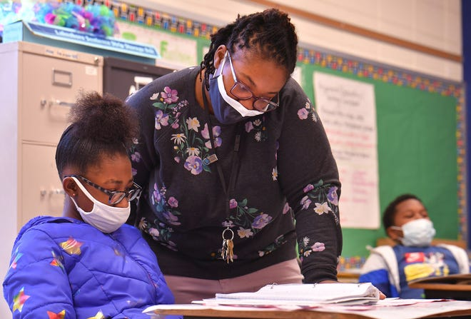 Fifth grade teacher Kenesha Hardy helps student Jahlysah Smith, left, as students work on posters in their classroom at Mary H. Wright Elementary School in Spartanburg, Thursday morning, March 3, 2021. The class is working on a project with the posters to create a virtual museum that they and their fellow students and parents can visit.