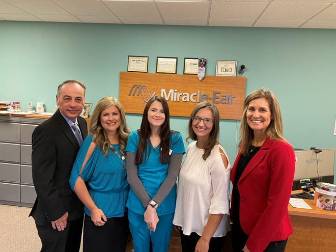 Kirksville Miracle-Ear staff members Tina Atchley (in white) and Alex Higgins (to her left) pose after receiving their Top Provider Team for 2020 award.