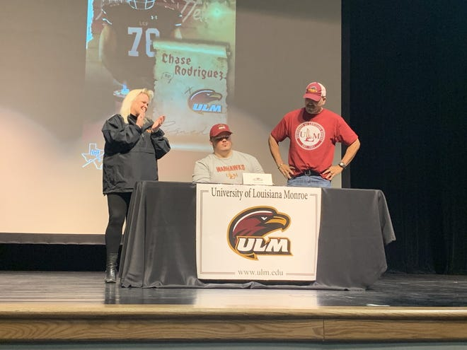 Lubbock-Cooper offensive guard Chase Rodriguez (center) participated in a signing ceremony after accepting a preferred walk-on spot at the University of Louisiana-Monroe on Thursday at Lubbock-Cooper High School's Performing Arts Center in Woodrow.