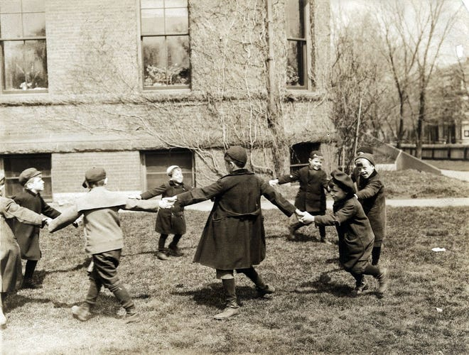 Students from the Kindergarten Department of the Perkins Institution and Massachusetts School for the Blind in Jamaica Plain are playing outside with their hands clasped, walking in a ring. This photo is from 1909. Learn more from Digital Commonwealth at www.digitalcommonwealth.org.