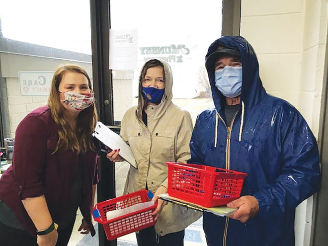 Pharmacist Madalyn Bell, from left,  Judy Stone Wilson,a Rotary'runner' and Larry Carigran Knight, parking coordinator, get to work at the first drive-in vaccine clinic at Munsey's Pharmacy in Oak Ridge.