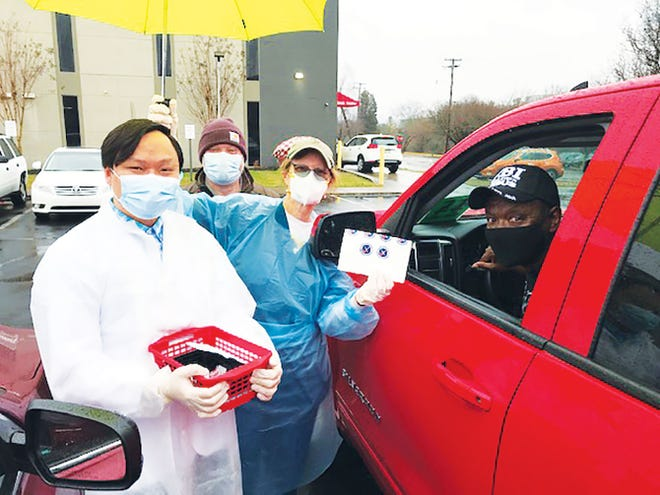 Pharmacist Duc Pham, from left, and Nancy Kyle, an advanced practice registered nurse, make sure an area resident gets the COVID-19 vaccine last Saturday, Feb. 27, with rain protection provided by a friend.