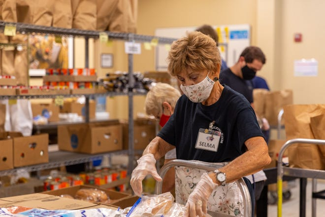 Volunteer Selma Lelling packs pantry bags in the Boca Helping Hands warehouse to distribute to residents in need. In 2020, the organization distributed more than 78,000 pantry bags.