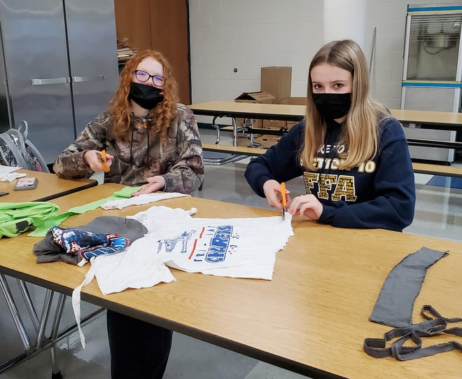 The Tri-Point FFA recently conducted a community service project in conjunction with a recent chapter meeting. Members recycled old t-shirts into woven dog toys which will be donated to area shelters and vet clinics. Kori Weber, left, and Cali Statler, right, are working to make their donation items.