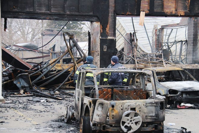 Personnel from the Pontiac Fire Department and Illinois State Fire Marshal's office discuss Thursday morning the fire that destroyed Bernie's Automotive the night before. Bernie's was totally destroyed by the two-alarm fire.