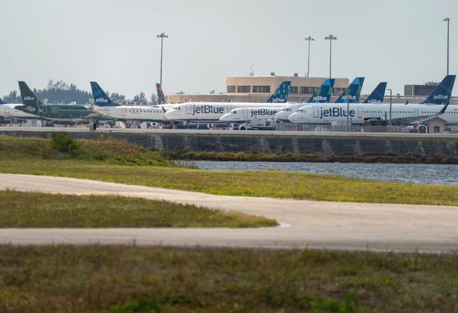 Jet Blue aircraft are parked at Palm Beach International Airport in West Palm Beach, Florida on April 9, 2020 as few flights are taking off since the coronavirus pandemic.  [GREG LOVETT/palmbeachpost.com]