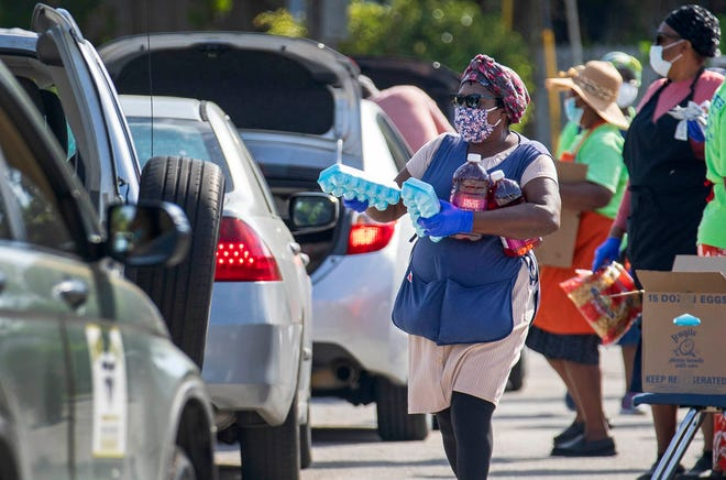 Volunteers with United Haitian Baptist Church's Food Ministry load cars with food from Feeding South Florida during a drive-thru distribution at the church in West Palm Beach Wednesday, March 3, 2021. The organization serves hundreds of people every Wednesday, from 9a.m. to 1p.m.