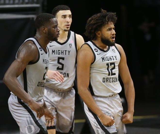 Oregon's LJ Figueroa (12) celebrates a play during the second half of Oregon's win over UCLA on March 3 as teammates Eugene Omoruyi and Chris Duarte (5) look on.