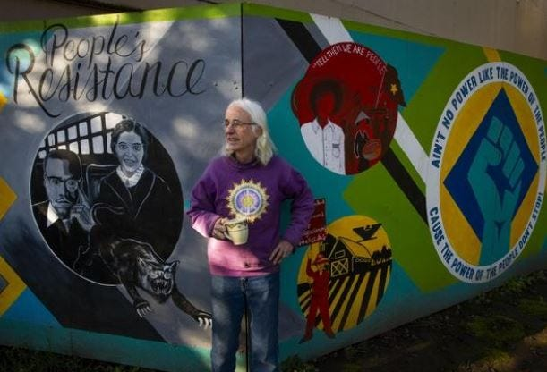 """Longtime Eugene volunteer and activist Michael Carrigan stands in front of the CALC """"People's Resistance"""" mural in March 2020. The mural was defaced in February 2021."""