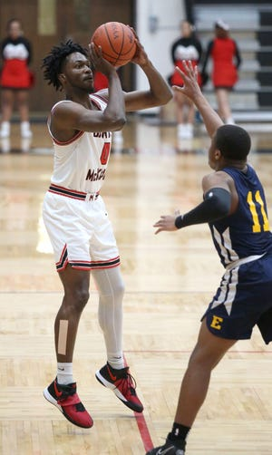 Kobe Johnson of McKinley takes a shot while being guarded by Clayton Cunningham of Euclid during their Division I district semifinal at Memorial Field House, March 3, 2021.