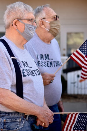 Gary Bitler and Eugene Rietbrock, residents of Residence 600, hold their flags prior to the ceremony to celebrate the 90th birthday of the national anthem on Wednesday afternoon.