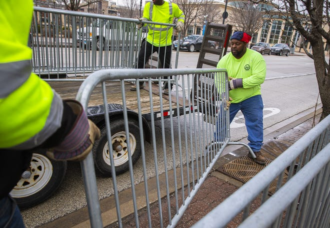 Aaron Pearl, with Springfield Public Works, helps load fencing back onto a trailer along Jefferson Street as crews pickup the preparations that had been put in place for the St. Patrick's Day parade after it was postponed because of the COVID-19 pandemic, Thursday, March 12, 2020, in Springfield, Ill. The 2021 parade also has been postponed because of pandemic concerns with large gatherings. [Justin L. Fowler/The State Journal-Register]
