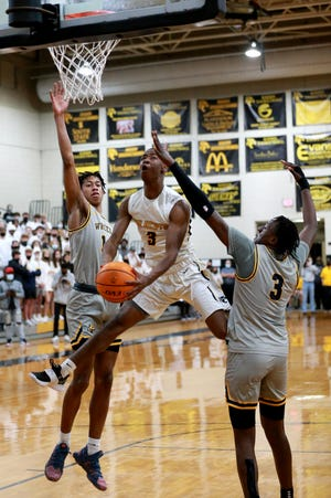 Richmond Hill's Nijajuan Youmans makes an acrobatic move to the basket between Wheeler's Kaleb Washington and Jahiem Hudson during Wednesday night's Class 6A state quarterfinal playoff game at Richmond Hill.