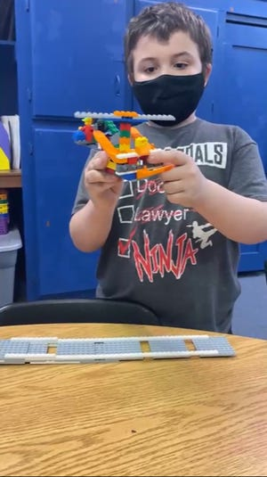 Horace Mann 3rd grade students were challenged to create original masterpieces from 100 Legos. William Prentice-Gay explains his original creation, a helicopter equipped with a tracking box and swivel seat for the pilot while being videoed by site Coordinator, Tammy Keller. Horace Mann and Jefferson Elementary Schools are in their final year of a 21st CCLC Grant.