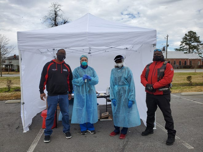 Victor Taylor of Vision Forward, left, and Jamal Williams, president of Burn City Motorcycle Club, are pictured with workers during a free COVID-19 testing event held last month in New Bern. [Tina Adkins, Sun Journal staff}