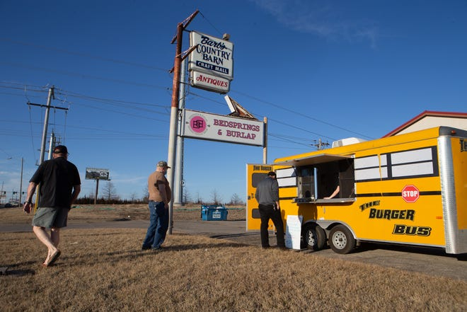 A line of customers await to order from the Burger Bus while it was parked Wednesday in front of Barb's Country Barn, 4008 S.W. Topeka Blvd.