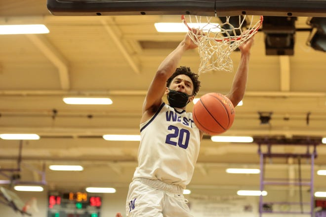 Topeka West senior Trevion Alexander dunks over Newton in the fourth quarter of Wednesday's Class 5A sub-state tournament at Topeka West. The Chargers won 71-60.