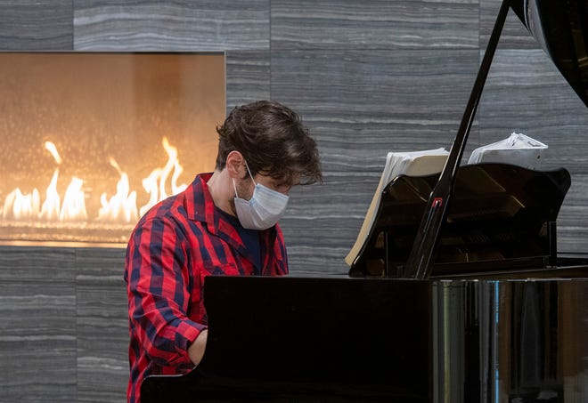 Brooks Milgate plays piano in the lobby of Mercantile Center March 4 as people arrive to receive their COVID-19 vaccinations.
