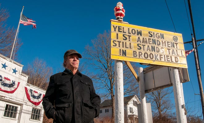 John D. Holdcraft stands by his sign on Route 9 in Brookfield.