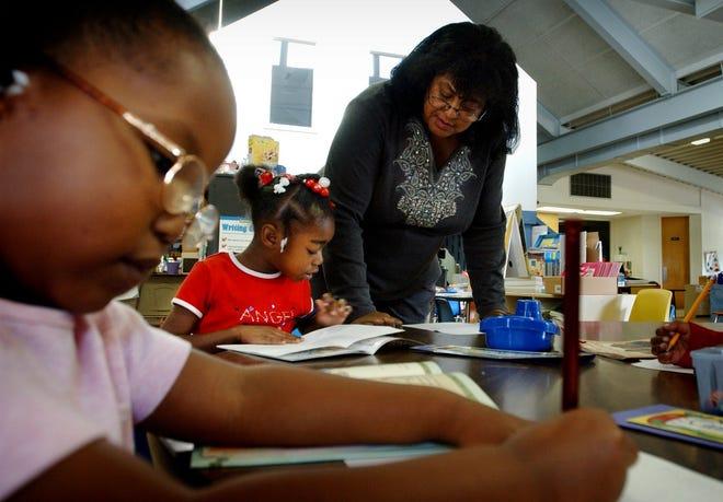 Substitute teacher Margaret Geddie, right, helps kindergartener Jasmine Accoo with her work. Geddie has been a substitute teacher at the school for five years.