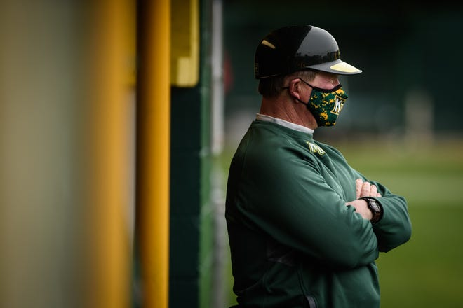 Methodist baseball coach Tom Austin watches his team from the dugout during their game against Lynchburg on March 2. Austin recently won his 1,200th game as the Monarchs' coach. He has more wins than any other active NCAA Division III baseball coach.