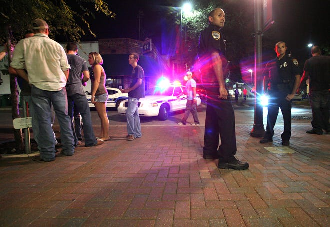 Gainesville Police Department Officers Rob Narayan and Justin Torres watch over pedestrians near Southwest Second Street on Sept. 3, 2010. GPD closes some downtown roads at 1:30 a.m. to protect people pouring out of bars and venues. [Gainesville Sun File Photo by Matt Walsh /Correspondent]