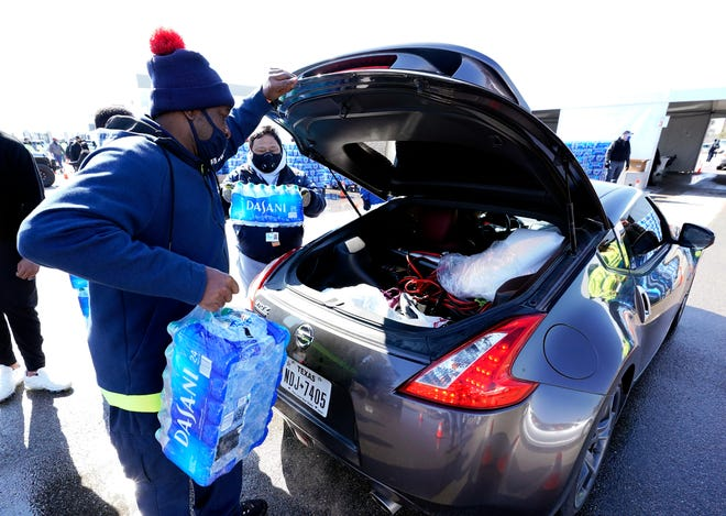 Bottled water is loaded into the trunk of a car in Houston on Feb. 19 at a site set up for those lacking water due to frozen or broken pipes after winter storms hit Texas.