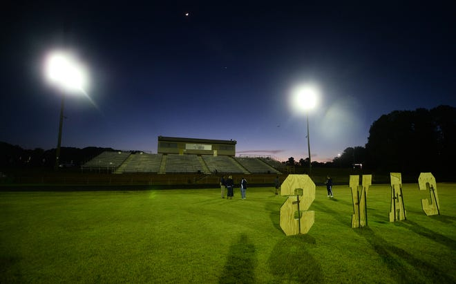The football stadium at Cummings High School is illuminated last April in honor of then-seniors who were unable to finish their spring sports seasons due to the coronavirus pandemic. Attendance for outdoor events has been increased to 30 percent of capacity.