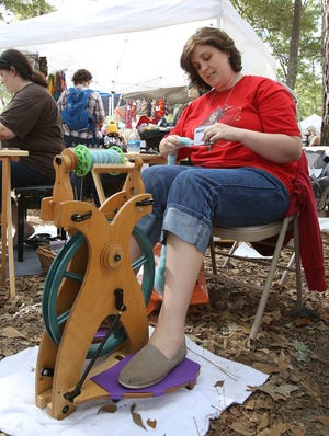 Jennifer Clark of the West Alabama Fiber Guild spins yarn during the Kentuck Festival of the Arts in downtown Northport in this 2016 file photo. This year's festival, the 50th, will feature the works of more than 270 artists on Oct. 16-17. [Staff file photo]