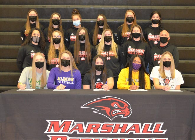 Five senior volleyball players at Marshall participated in a signing ceremony as they committed to playing at their respective colleges. Sitting, from left, Olivia Webber, Courtney Fuller, Teagan Giannunzio, Ja'Nyece Larry and Abby Welke are joined by teammates and coaches at Marshall High School on Wednesday.