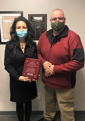 Board of Health President Zach Wolfe presents the 2020 Public Health Partner of the Year plaque to Jette Cander, Crawford County EMA director.