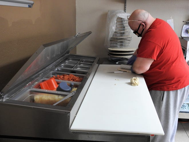 Larry Young of Dany's Pizzeria makes dough for pizzas. The shop and Daily Bread Bakery, both owned by Danyelle and Terry Darr, received funding from the Port Authority and county to keep going during the COVID-19 pandemic.